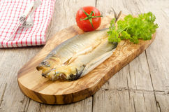 Smoked kipper with tomato and parsley. On a wooden board Stock Image