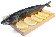 Smoked mackerel. With lemon on trencher Royalty Free Stock Photography