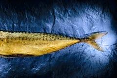 Smoked mackerel on black stone slab. View from above. Stock Photos