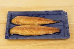 Smoked mackerel in a carton. On a wooden worktop royalty free stock photos