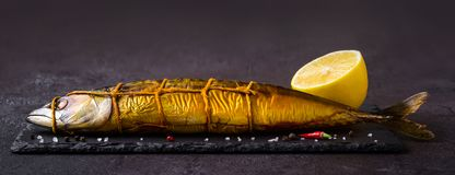 Smoked mackerel fish on black stone cutting board, banner format stock image