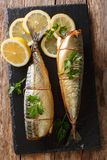 Smoked mackerel with lemons and parsley closeup on a slate board on the table. Vertical top view stock photos