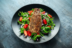 Smoked Mackerel Salad with tomato, chopped red onion, Ruccola on black plate. Royalty Free Stock Images