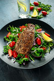 Smoked Mackerel Salad with tomato, chopped red onion, Ruccola on black plate. Stock Images