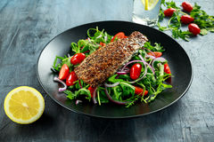 Smoked Mackerel Salad with tomato, chopped red onion, Ruccola on black plate. Royalty Free Stock Image