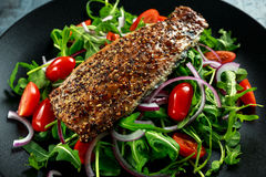 Smoked Mackerel Salad with tomato, chopped red onion, Ruccola on black plate. Royalty Free Stock Photography