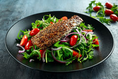 Smoked Mackerel Salad with tomato, chopped red onion, Ruccola on black plate. Stock Image