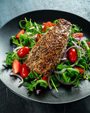 Smoked Mackerel Salad with tomato, chopped red onion, Ruccola on black plate. Royalty Free Stock Photo