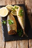 Smoked mackerel snack food served with lemons and parsley closeup on a black stone board. vertical stock photos