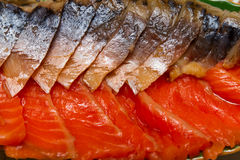Smoked mackerel and trout cut on a platter closeup Royalty Free Stock Photography