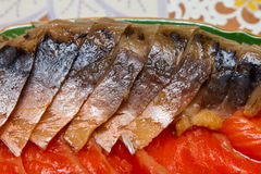 Smoked mackerel and trout cut on a platter closeup Stock Photos