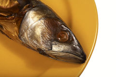 Smoked mackerel. On a yellow plate royalty free stock photo