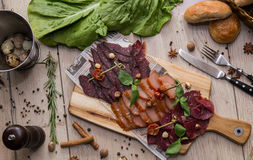 Smoked meat. Board with smoked meat and greens royalty free stock photo