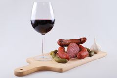 Smoked meat bratwurst and glass of red wine Royalty Free Stock Photo