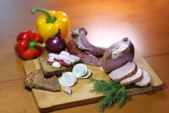 Smoked meat. Smoked bacon, sliced on a wooden plank. royalty free stock images