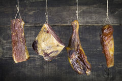 Smoked Meat Hanging on the Rope Against Wooden Background royalty free stock images