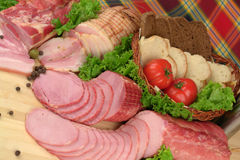 Smoked meat products. Smoked Ham smoked bacon with greens & vegetables stock photo