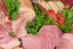 Smoked meat products. Smoked Ham smoked bacon with greens & vegetables royalty free stock photo