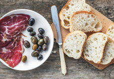 Smoked meat or prosciutto and olives on a white plate, vintage knife, baguette slices over rough wood background Royalty Free Stock Photography