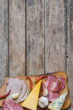 Smoked Meat, Sausage and Cheese. Delicious smoked meat, sausage and cheese on wooden board, tasty eating Stock Photos