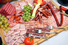Smoked meat and sausage on a wooden board Stock Images