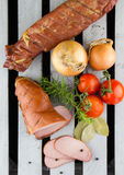 Smoked meat served with tomatoes and onions. Apple wood smoked pork loins. Sliced meat and vegetables. Sliced smoked pork. Electric smoker. Wood smoked meat stock photos