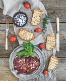 Smoked meat in vintage silver plate with fresh basil, cherry-tomatoes and bread slices over rustic wood Royalty Free Stock Photography
