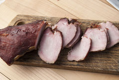 Smoked meat on wooden cutting board Stock Photo
