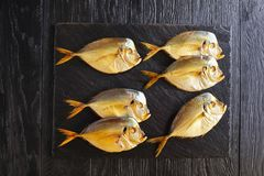 Smoked moonfish on black stone tray. Delicious cold smoked moonfish on black stone tray on black wooden table, view from above Royalty Free Stock Image