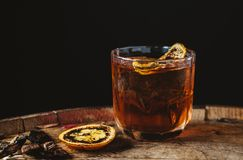 Smoked old fashioned cocktail on dark wooden background. Smoked old fashioned cocktail garnished with an orange peel on dark wooden background stock images