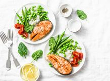 Smoked paprika baked salmon, rice, green peas and green beans on a light background, top view. Flat lay. Healthy balanced mediterr