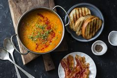 Smoked paprika lentil soup with grilled cheese sandwiches and crispy bacon on a dark background, top view. Delicious comfort food. Concept. Flat lay Stock Image