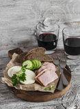 Smoked pork, cheese and two glasses of red wine on a light rustic wood background. Stock Images