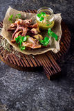 Smoked pork ears with mustard sauce on chopping board. Royalty Free Stock Photo