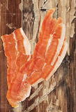 Smoked Pork Ham Prosciutto Slices on very Old Varnished Cracked Peeled Wooden Table Stock Image