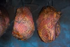 Smoked pork meat in smoker on dark background. A pork ham prepared in tradiional eastern European way of cooking in smoke stock photo