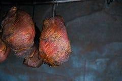 Smoked pork meat in smoker on dark background. A pork ham prepared in tradiional eastern European way of cooking in smoke stock images