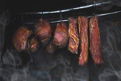 Smoked pork meat in smoker on dark background. A pork ham prepared in tradiional eastern European way of cooking in smoke royalty free stock image