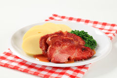 Smoked pork neck with potato dumplings and spinach Royalty Free Stock Photography