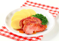Smoked pork neck with potato dumplings and spinach Stock Photo