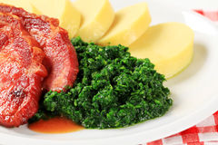Smoked pork neck with potato dumplings and spinach Stock Image