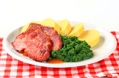 Smoked pork neck with potato dumplings and spinach Stock Photography