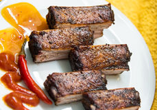 Smoked pork ribs with red pepper on the board Royalty Free Stock Image
