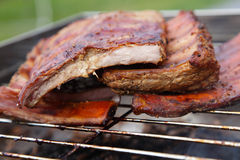 Smoked pork ribs on a smoker grill Royalty Free Stock Images