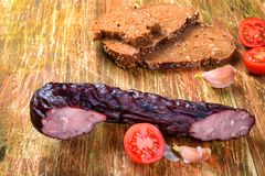 Smoked pork sausage with black bread, tomatoes and garlic. Smoked pork sausage with black bread, tomatoes and garlic on the rustical wooden background Stock Photo