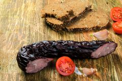 Smoked pork sausage with black bread, tomatoes and garlic. Smoked pork sausage with black bread, tomatoes and garlic on the rustical wooden background Stock Images