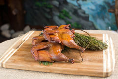 Smoked quail, partridges, chickens on a wooden. Board whole, with fir branch close-up, sacking and blue background Stock Photos