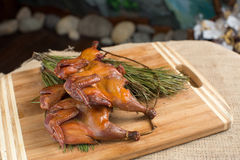 Smoked quail, partridges, chickens on a wooden. Board whole, with fir branch close-up, sacking and blue background stock images