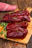Smoked red deer maral filleted on a wooden background. Close-up Royalty Free Stock Photos