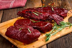 Smoked red deer maral filleted on a wooden background. Close-up Stock Photo
